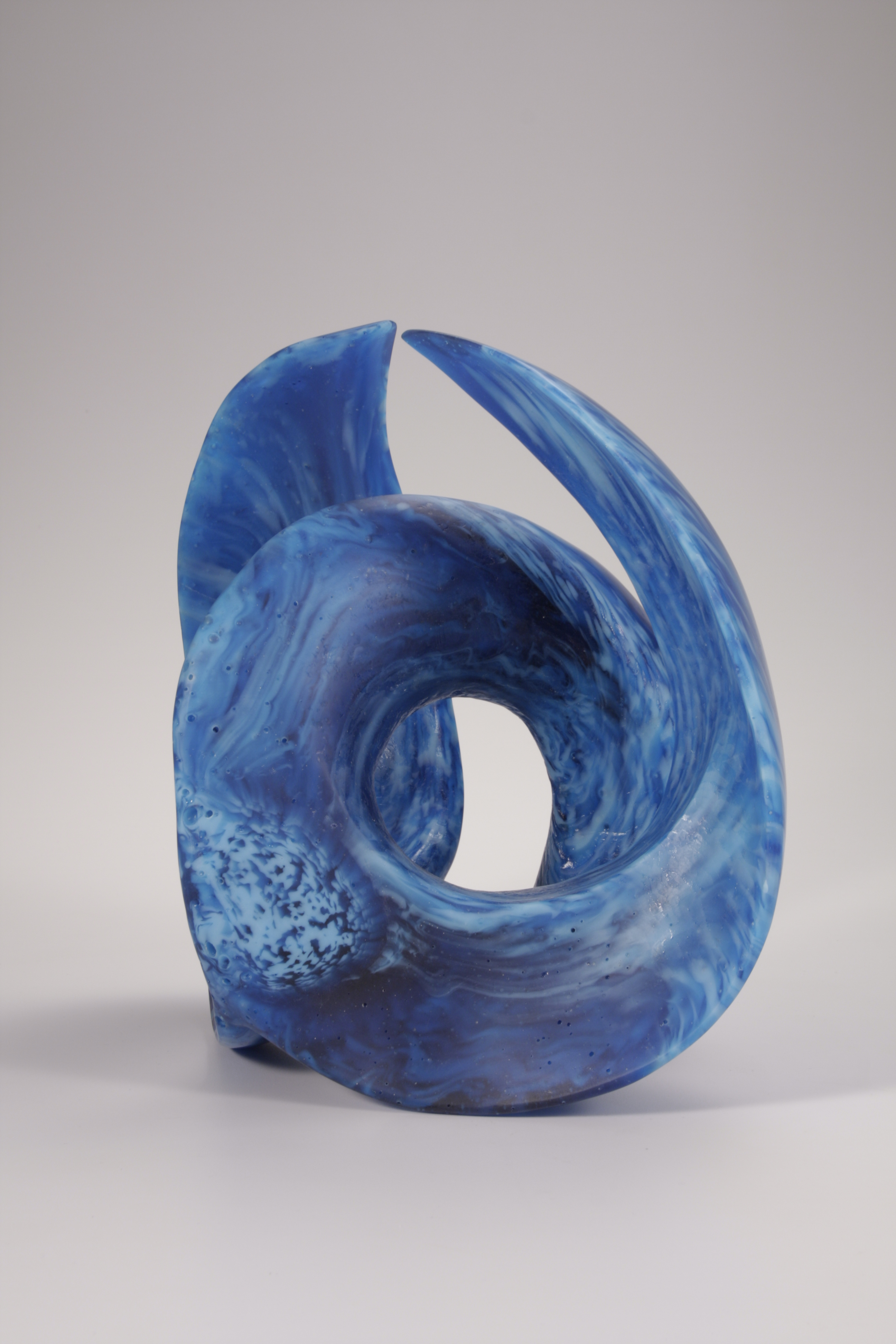 Sculpture of cast glass wave form in turquoise and light blue, side view.