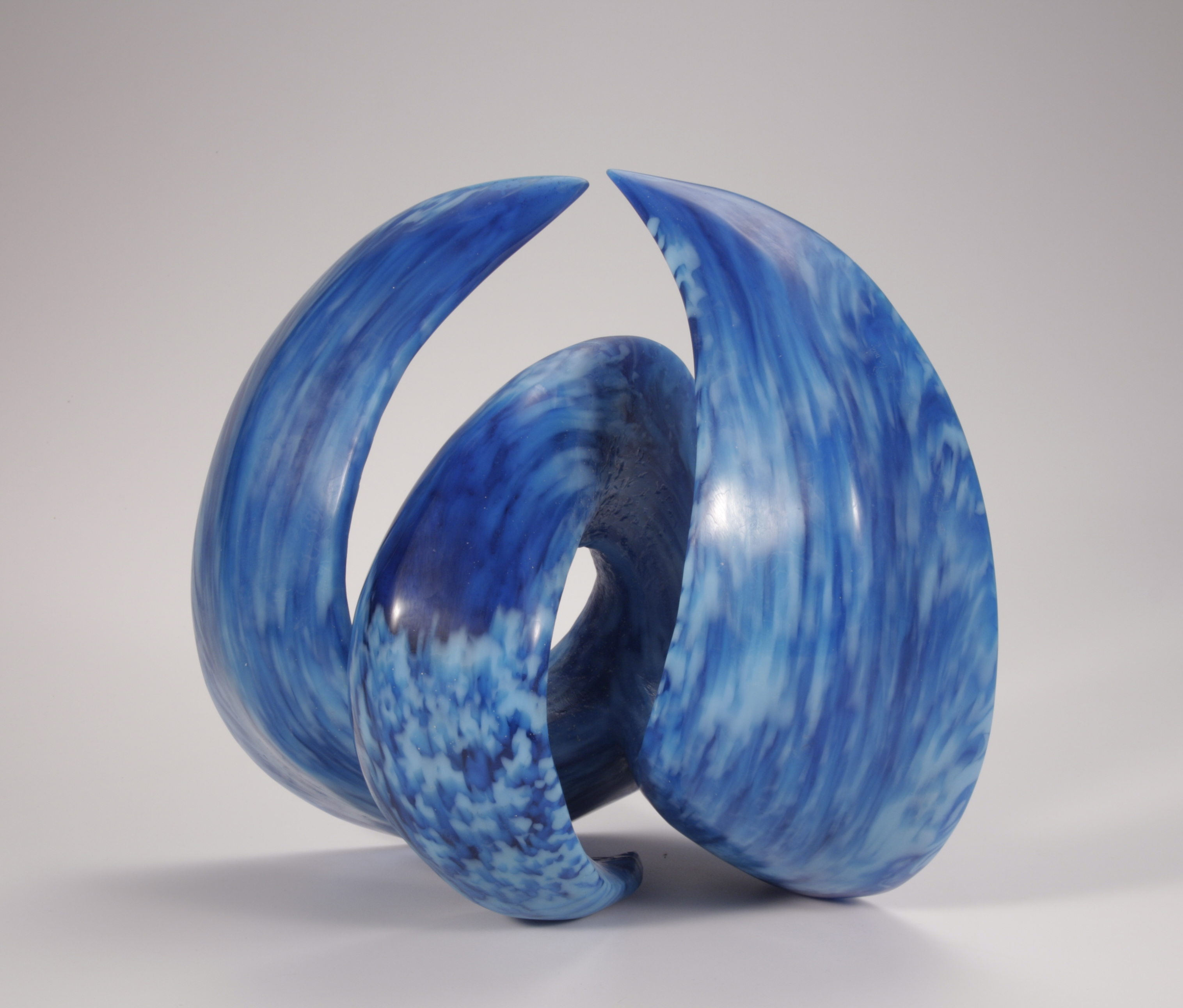 Sculpture of cast glass wave form in turquoise and light blue.