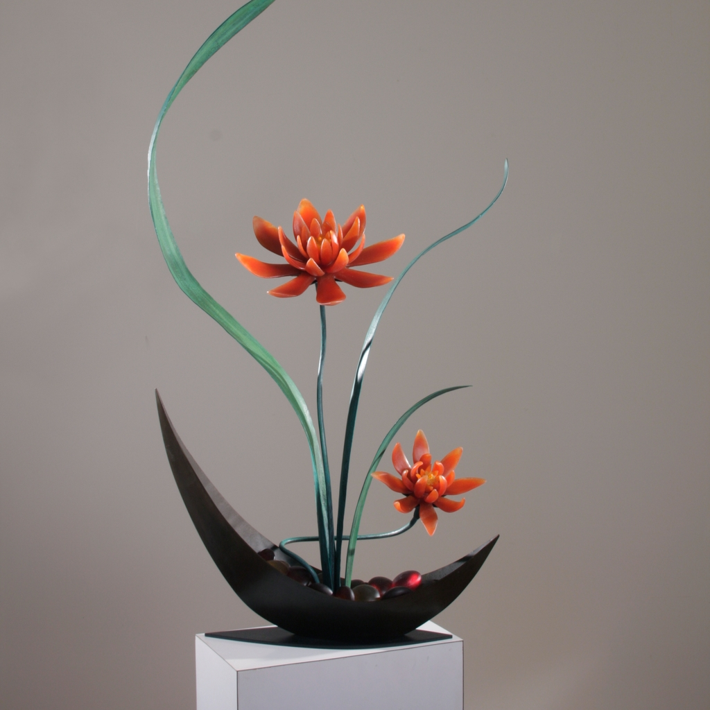 Sculptural flower arrangement in cast glass with red-orange flowers, green steel leaves, vase in deep brown.