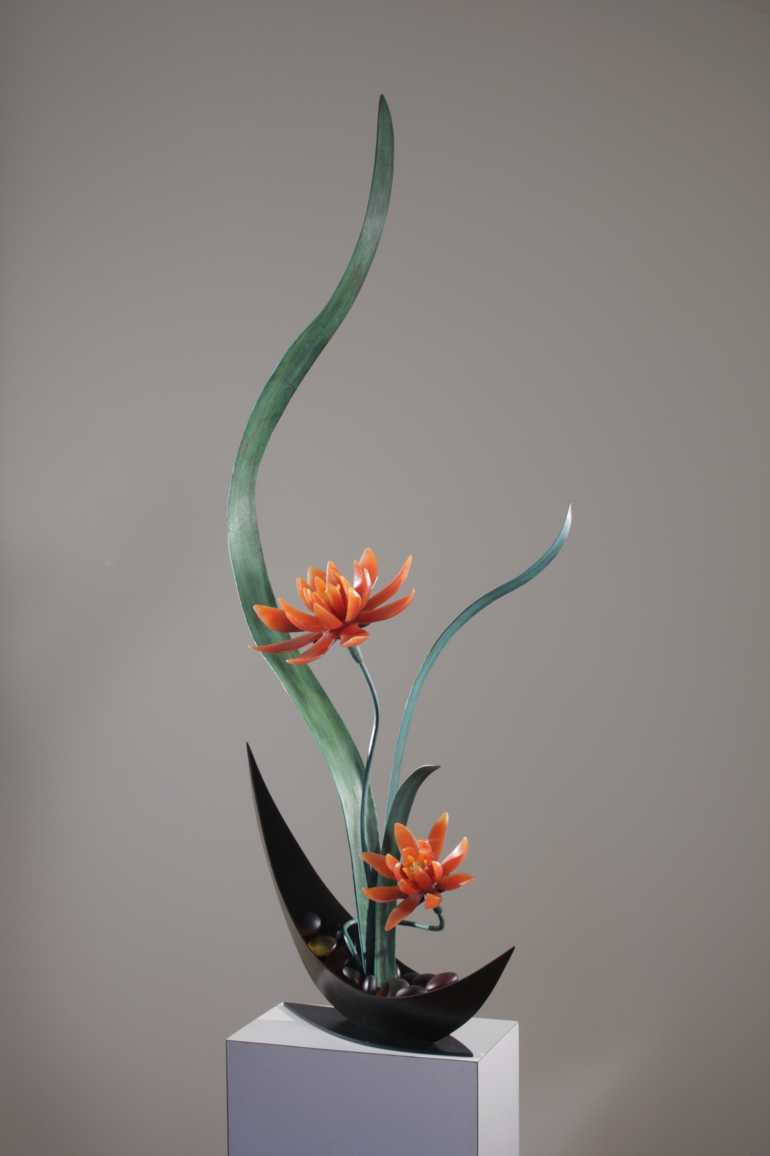 Angled view of sculptural flower arrangement in cast glass with red-orange flowers, green steel leaves, vase in deep brown.
