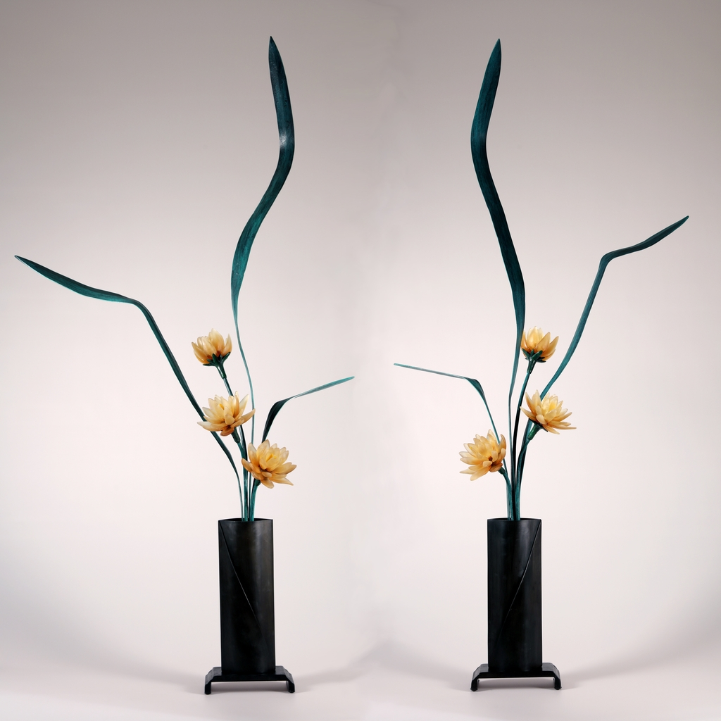 Sculptural flower arrangement in cast glass with amber flowers, green steel leaves, tall vase in deep brown.