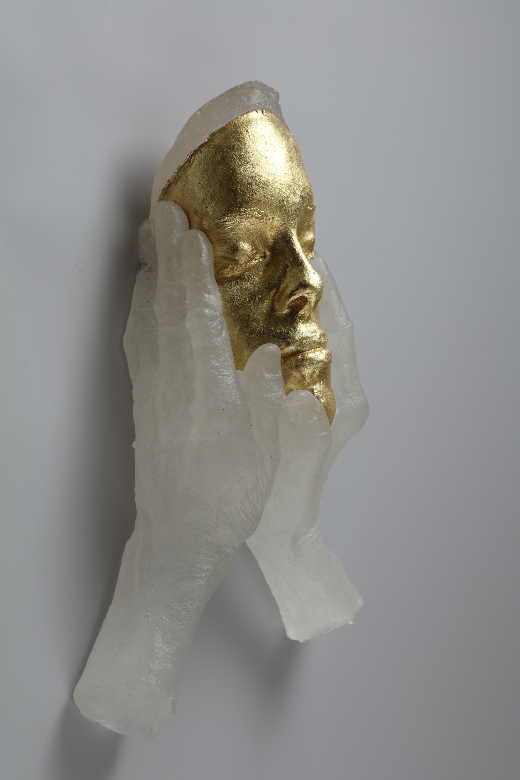 Sculpture of young face with old hands on it.