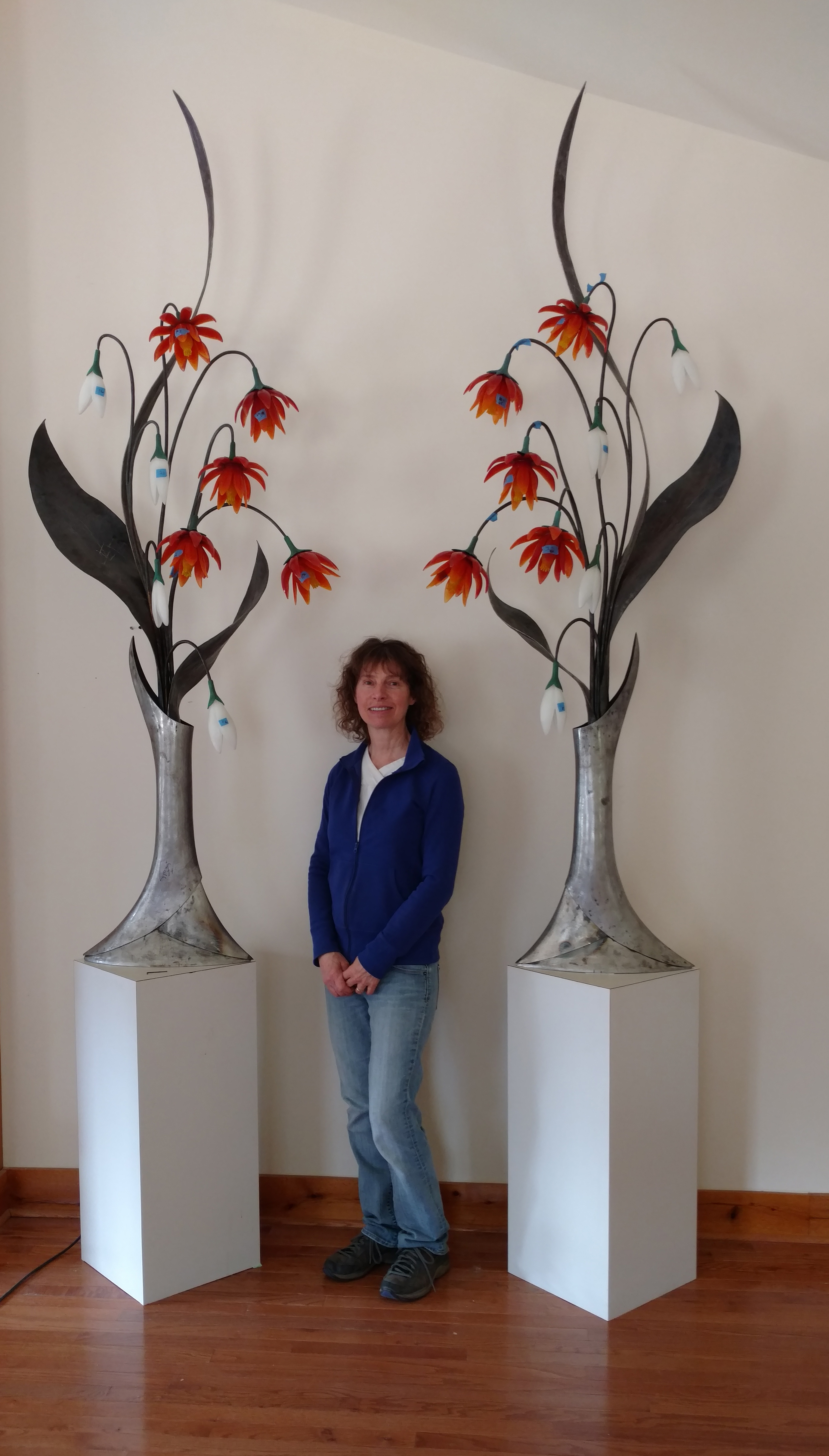 Sculpture of two seven and a half feet tall glass and steel flower arrangements shown with standing person for scale.