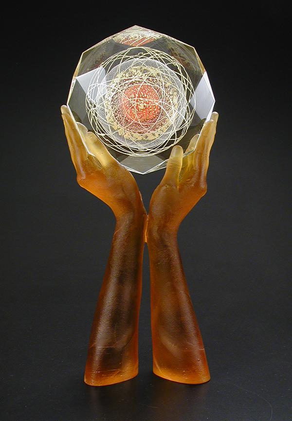 Cast glass hands holding a large glass gem.
