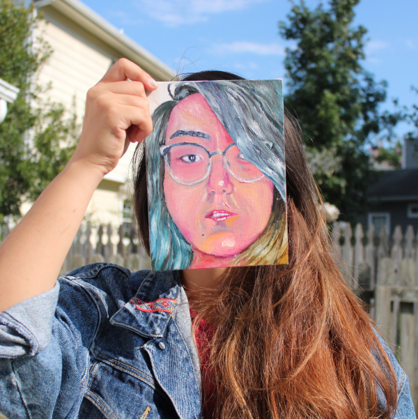 photo of me, holding a self-portrait painting in front of my face