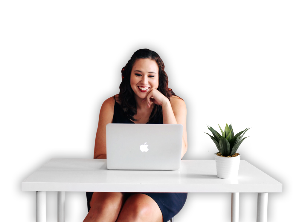Photo of a woman sitting at a desk on her laptop.