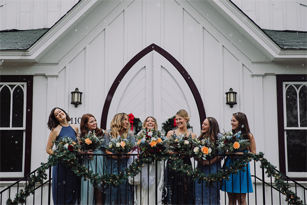 all-saints-chapel-bridal-party-on-stairs-in-snow