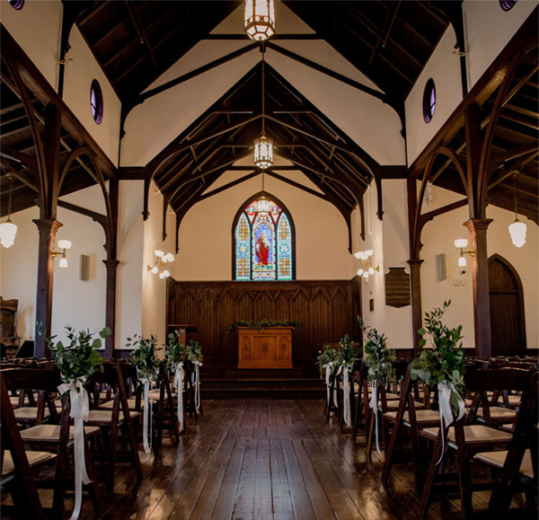 all-saints-chapel-aisle-flowers-on-chairs