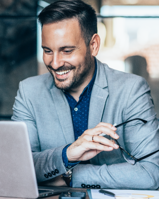 Man smiling while working on computer