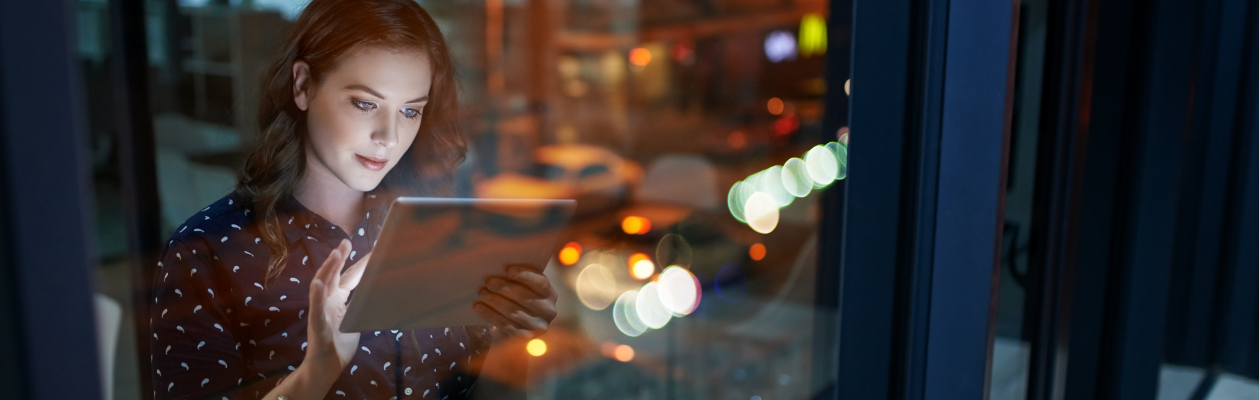 Woman standing in office window working on a tablet at night
