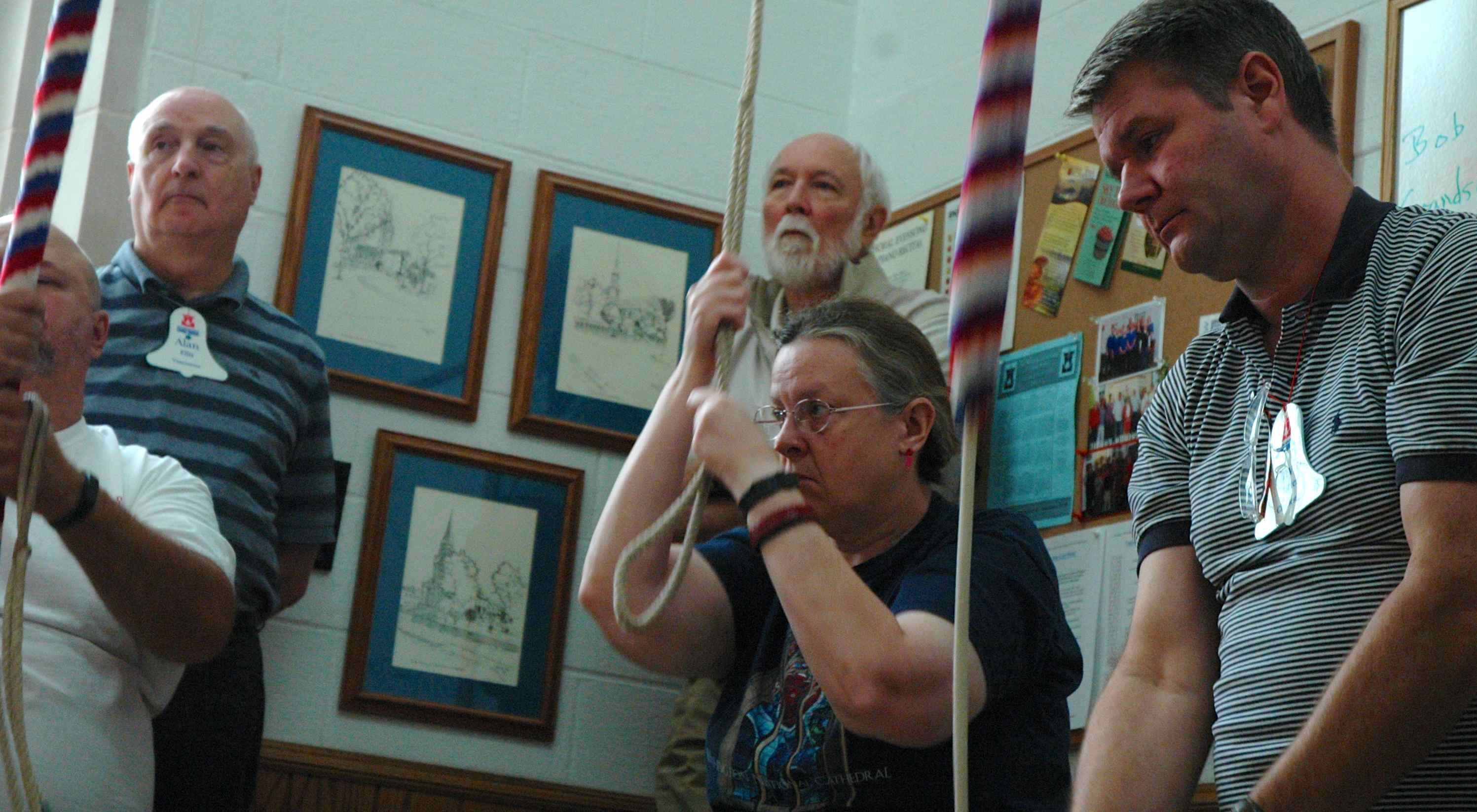 Three ringers in action pulling ropes with looks of concentration. Two observers standing behind.