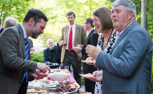 Smartly dressed ringers chatting and smiling while gathered standing around a table of food.