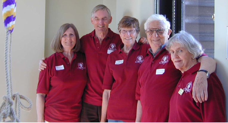 Five senior ringers in matching polo shirts smile for the camera in a ringing chamber.
