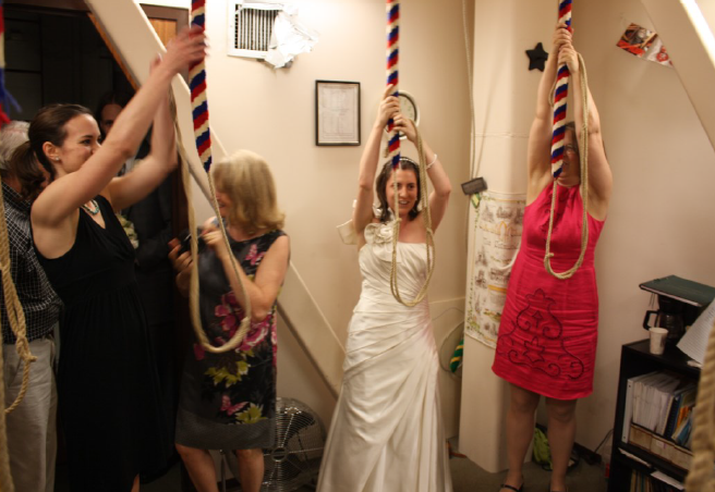 A bride, in a wedding dress, with two well-dressed wedding guests, about to pull their ropes to ring bells.