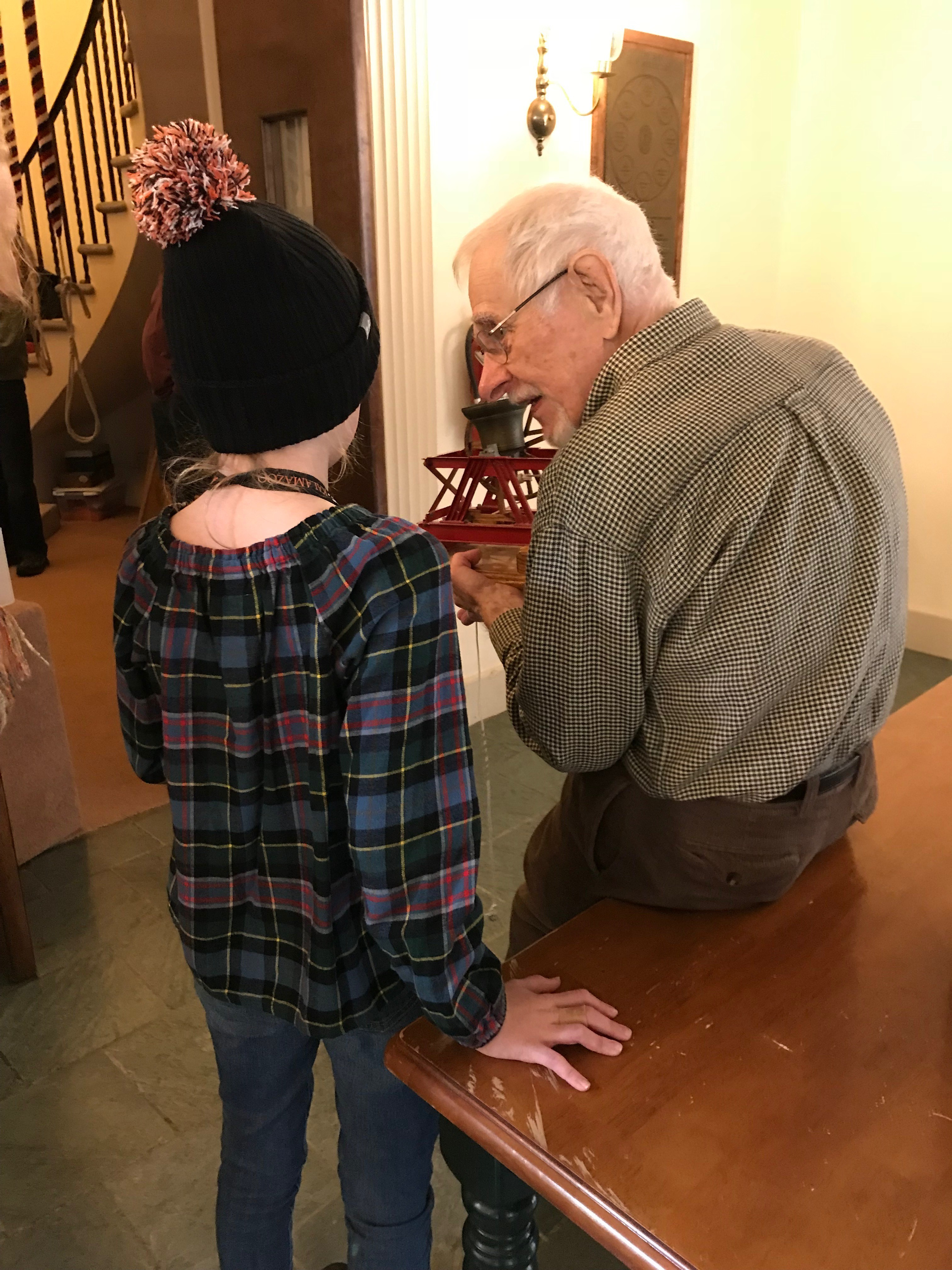 An older ringing explaining to a young girl of about 12 how a tower bell works.