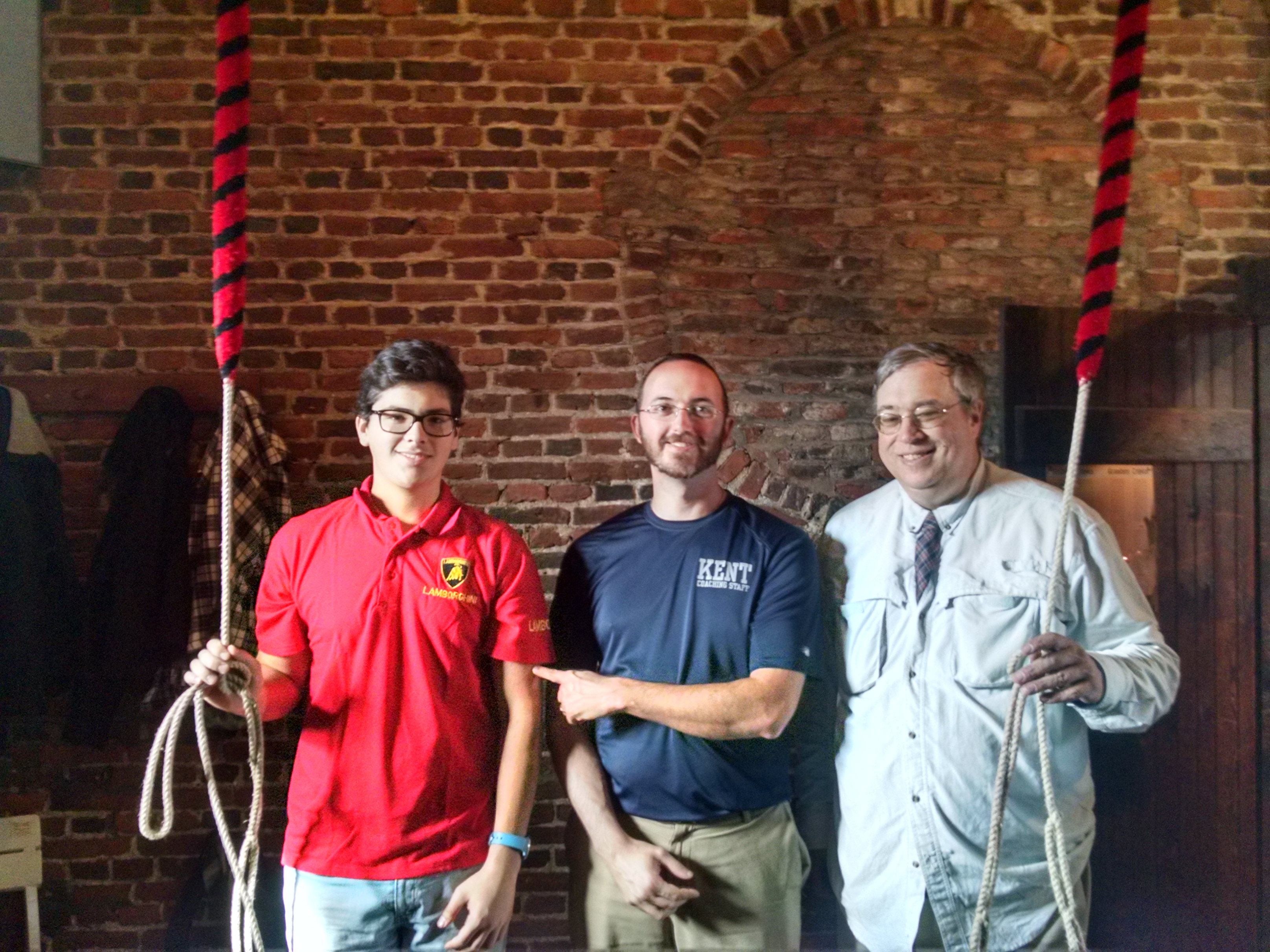A young man, a middle age man playfully touching his arm, and an older man, standing and smiling in a ringing chamber with ropes.