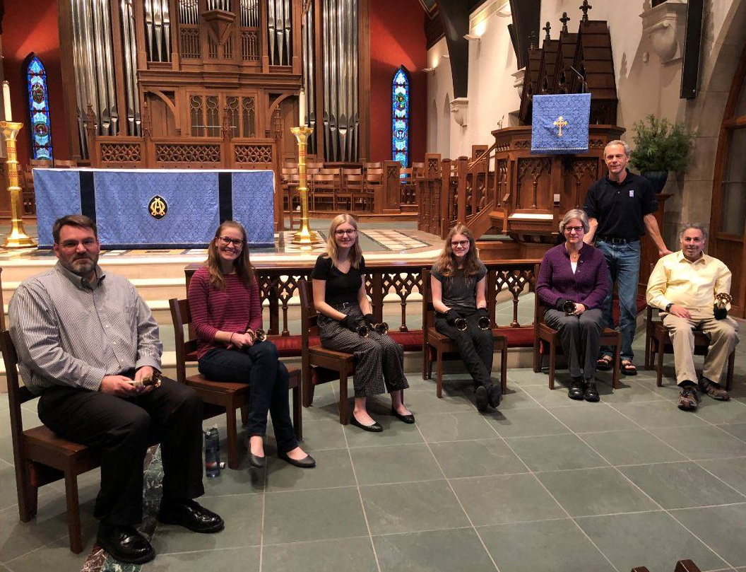 Six ringers seated with handbells, with their leader standing behind, all smiling.