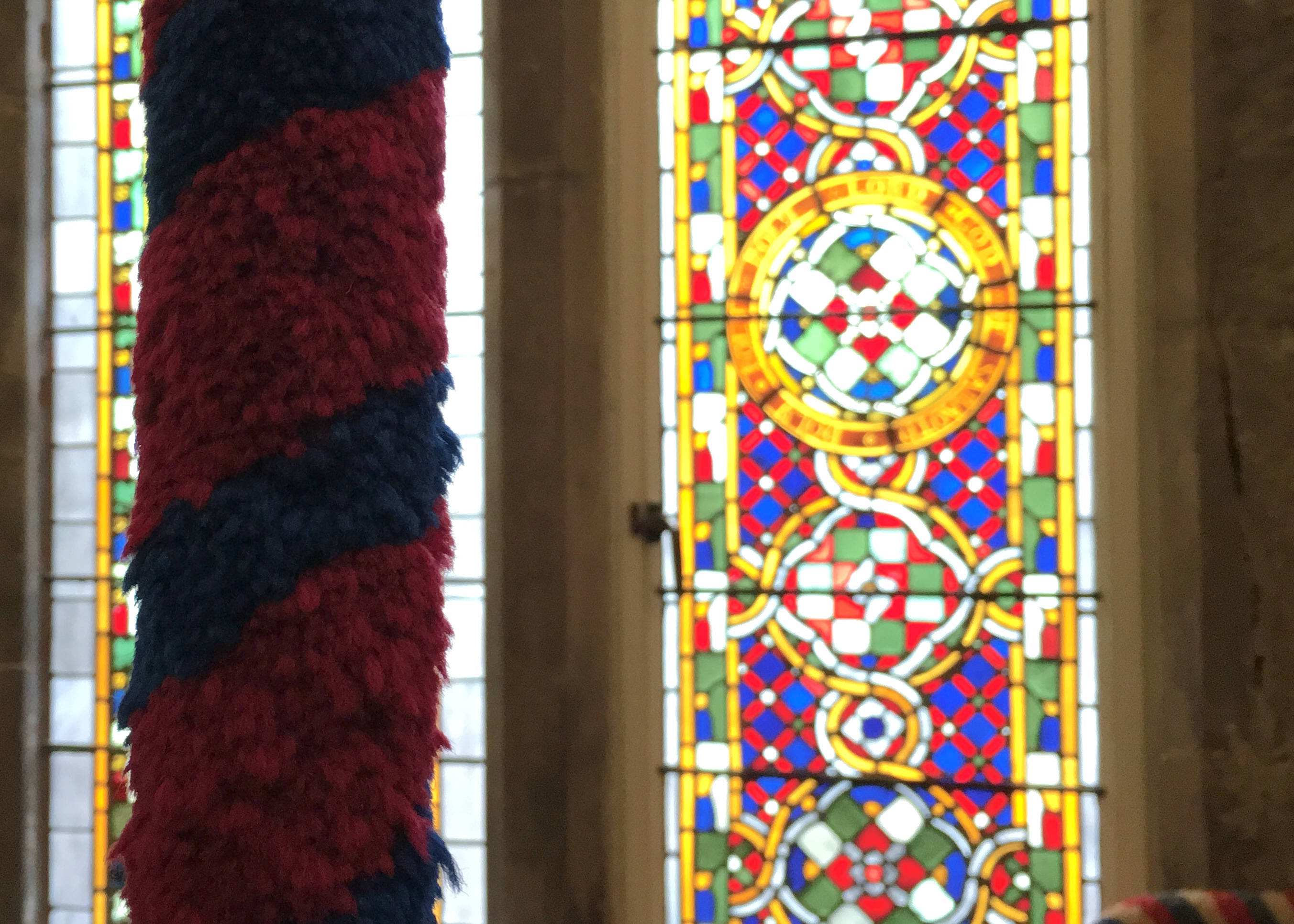 A colorful woolen sally from a bell rope in the foreground, with a stained glass window in the background.