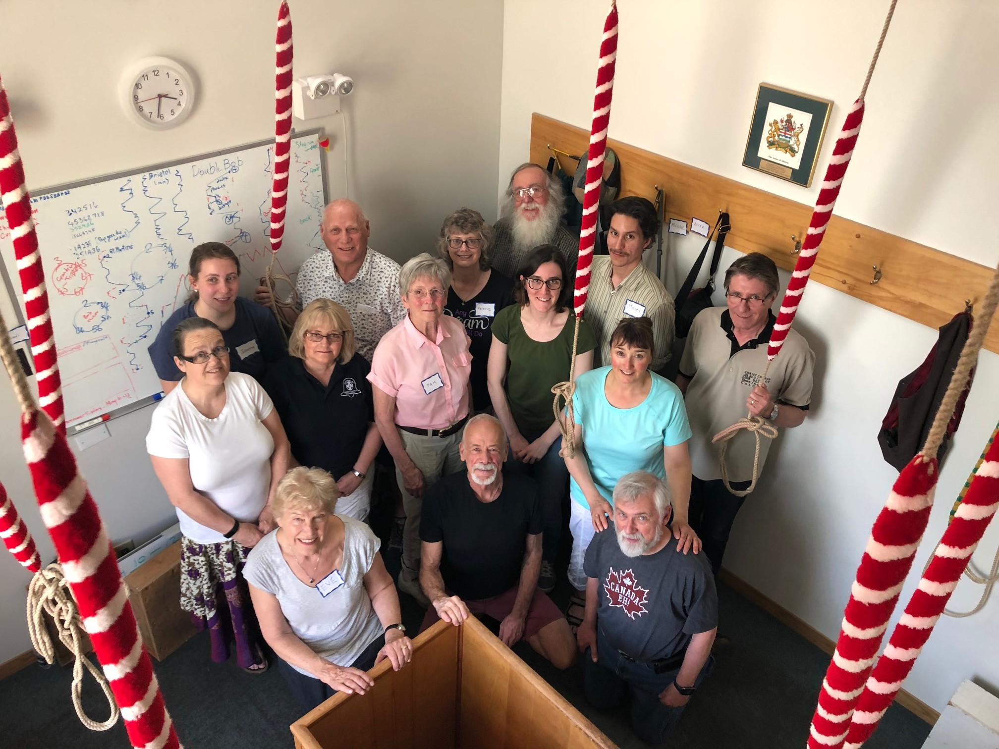 A group of about a dozen ringers of various ages in a bell tower, standing and facing up at the camera.