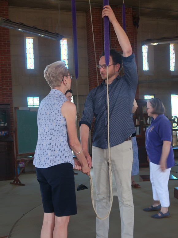 A young man holding a bell rope in one hand, facing a senior woman, helping her hold the rope properly.