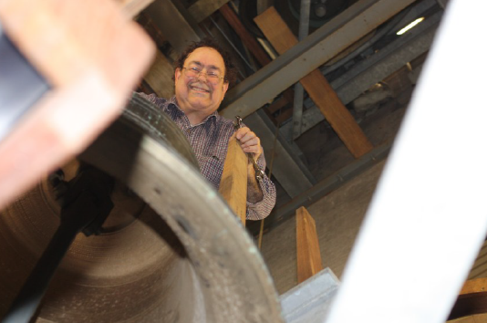 A man in a belfry leans over the top of a large bell, smiling and looking down at the camera