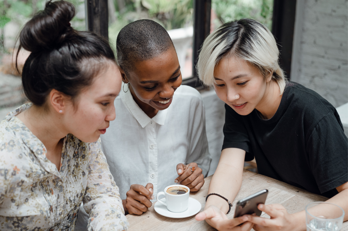 A group of three people at a coffee shop looking at a phone together