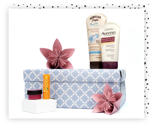 A box wrapped in blue gift wrap with bottles of lotion and lip balm placed around.