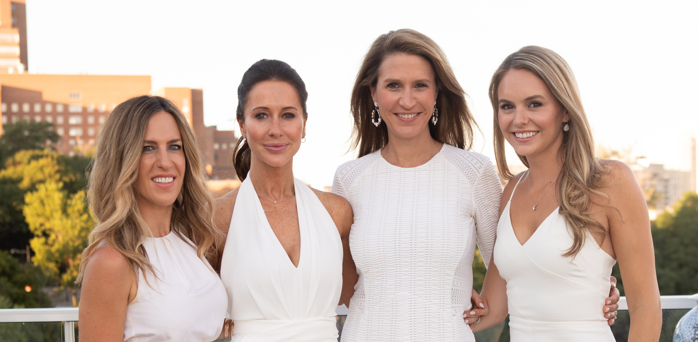 Four sisters in white dresses standing together.