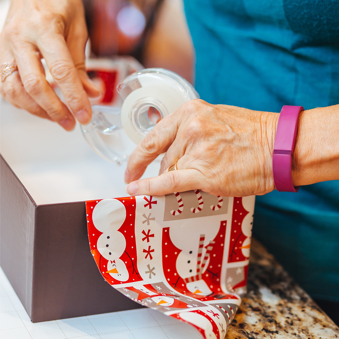 Hands taping wrapping paper to a Shoebox