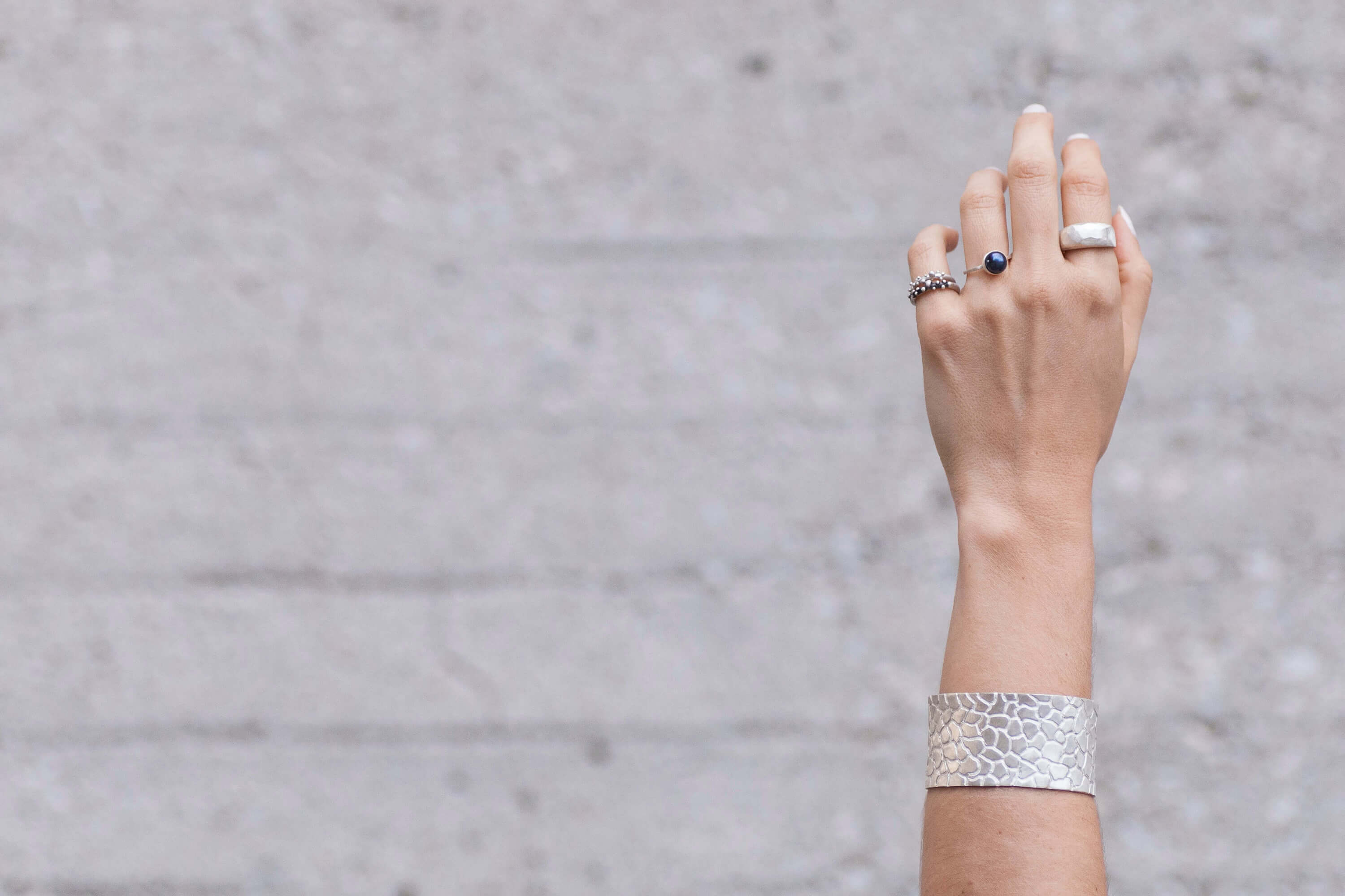 Hand with two thin bubble rings, one black pearl ring, one polygon ring and a bracelet on