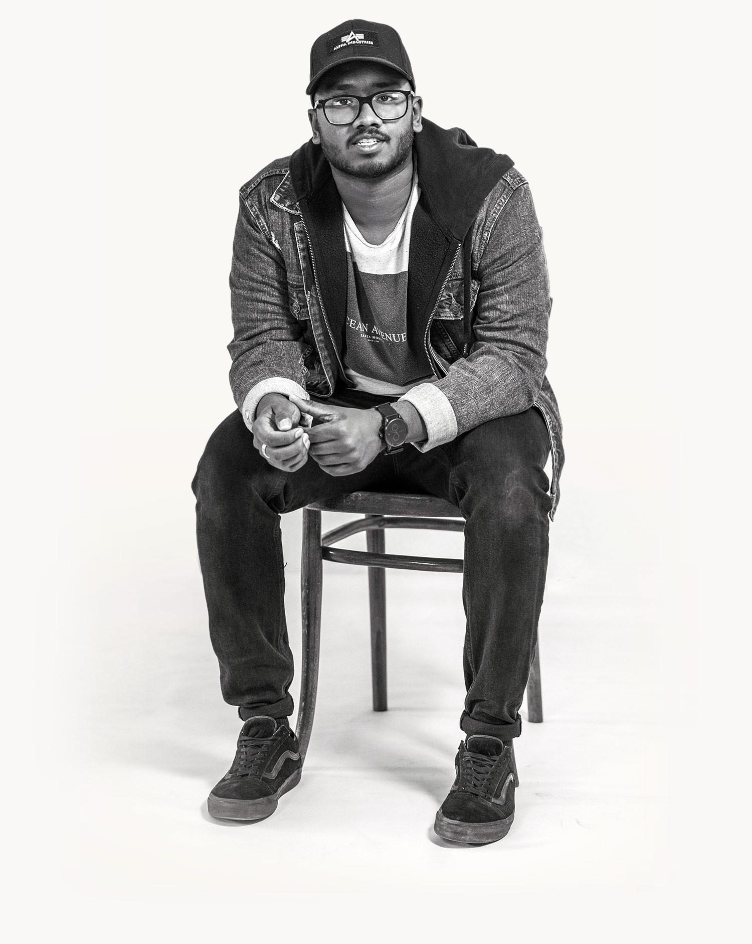 Junger Mann der auf einem Stuh sitzt und lächelt