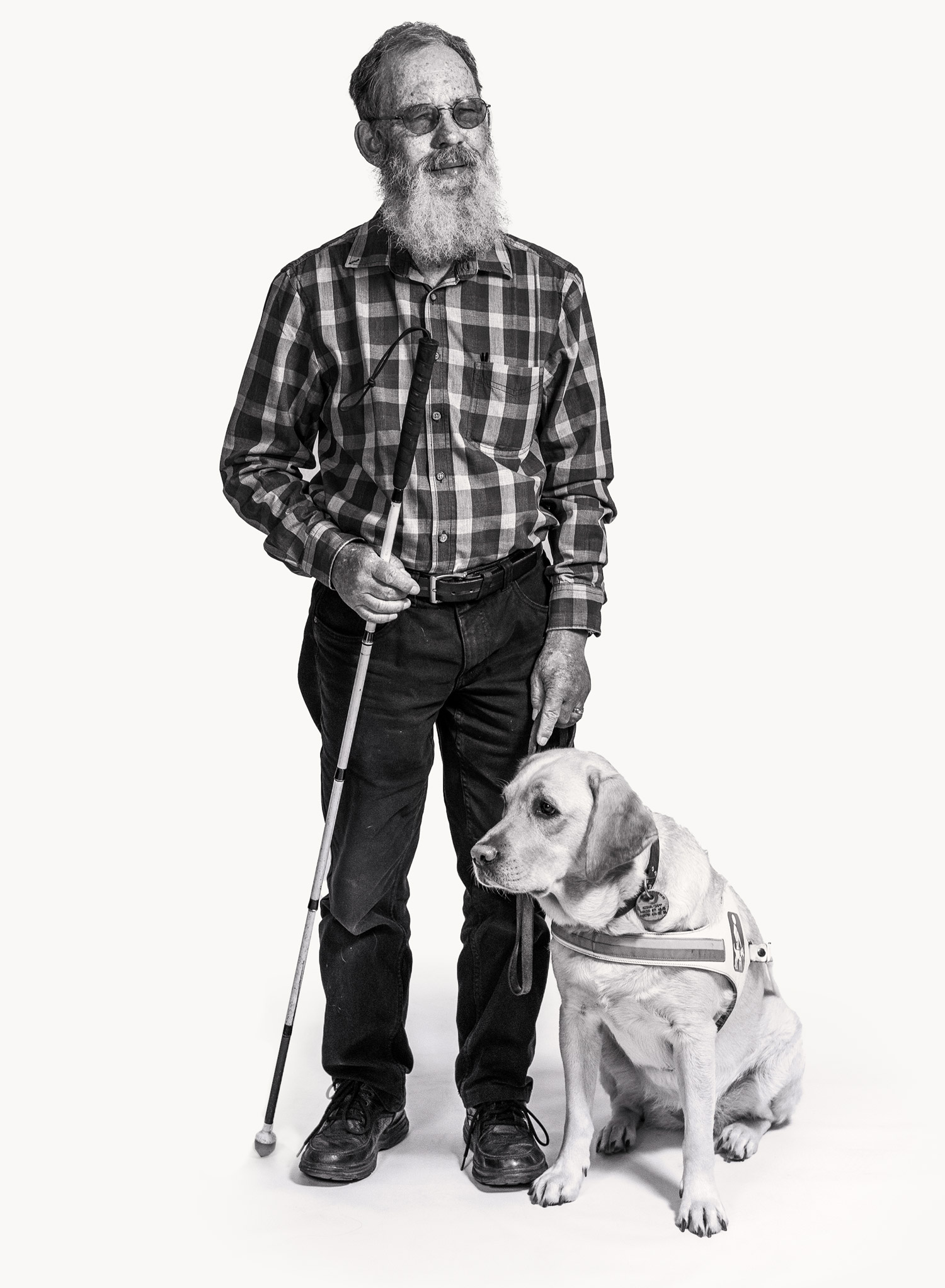 Stehender, blinder Mann mit seinem Blindenhund