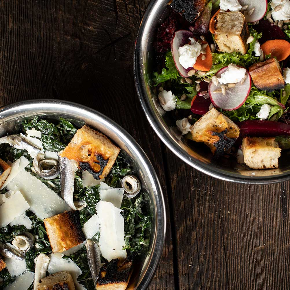 Top-down view of the Mixed Lettuces Salad and the Kale Caesar Salad.