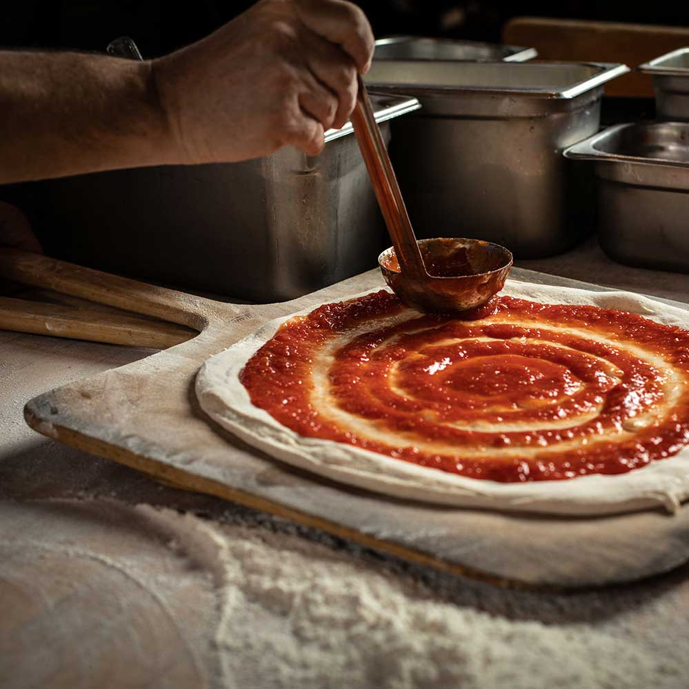 A person making sourdough pizza, spreading the sauce over the dough.