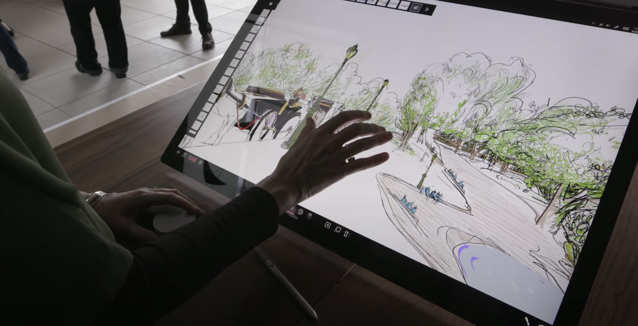 Shows a large Microsoft Surface tablet and an artists hand touching the screen.  The screen shows a Mental Canvas drawing of Central Park.