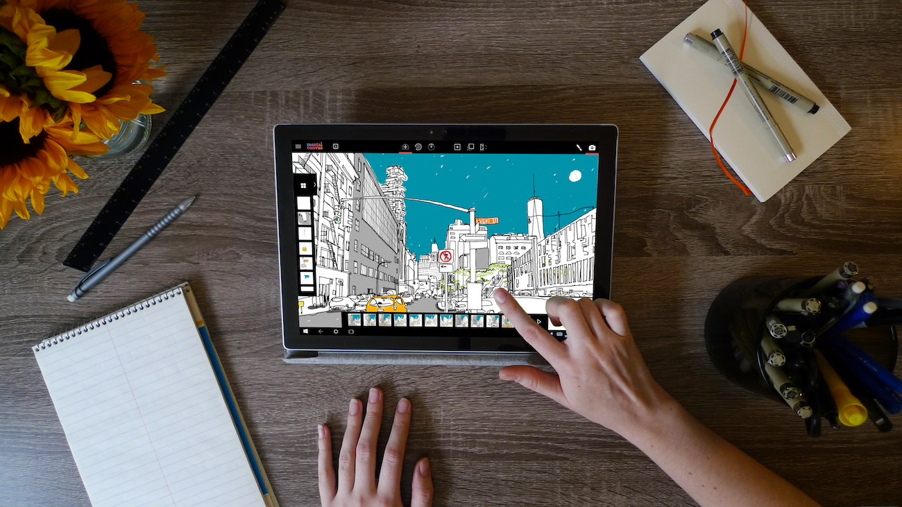 Shows a desktop with a Microsoft surface tablet running Mental Canvas software.  The pictures shows a woman's hand touching the screen and several desk items around the tablet.