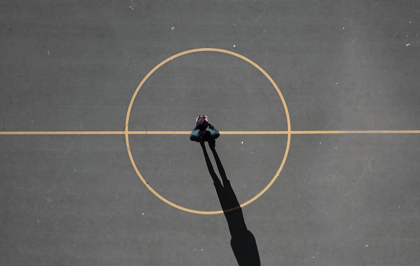 A photo of a man standing in the middle of a circle at the center of a basketball court