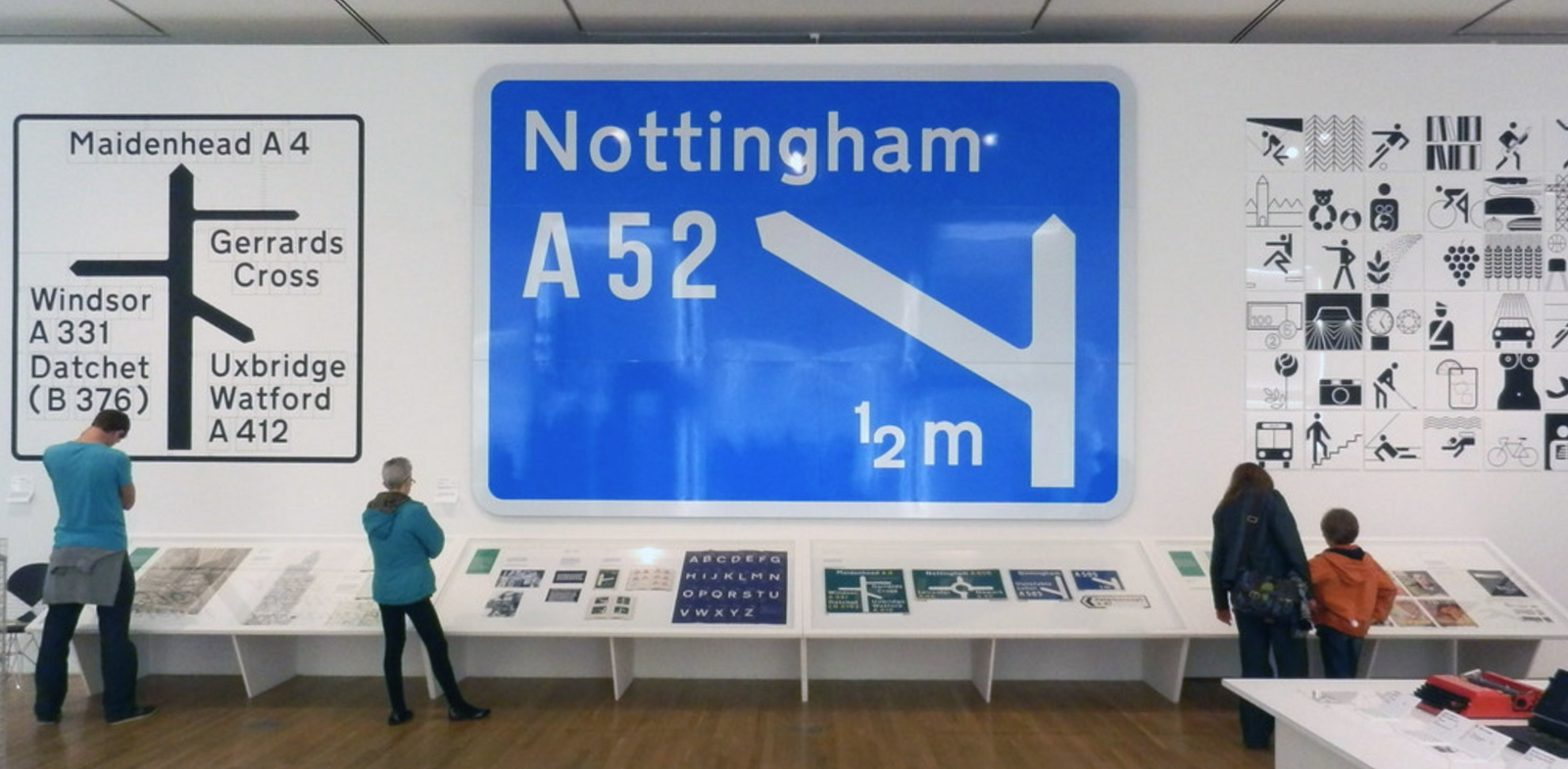 A photo of a few people looking at road signs by Kinneir and Calvert at the Design Museum, London