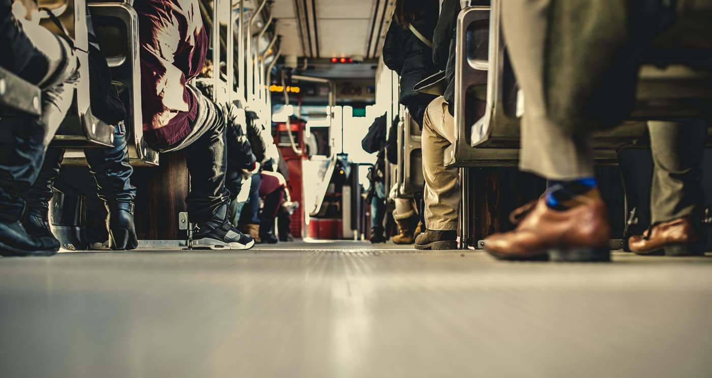 A photo of lots of people sitting on a bus but we only see their feet and legs.