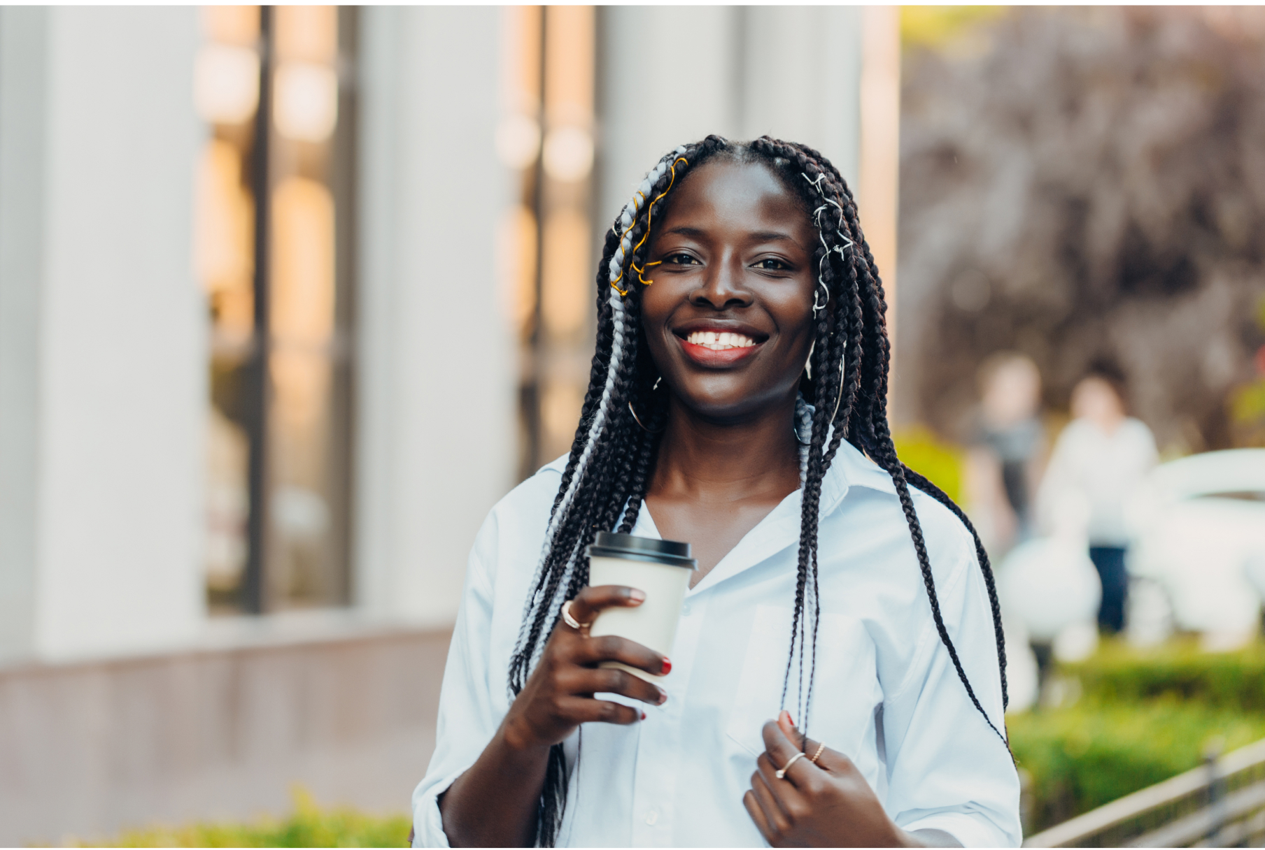 An african american young adult, woman, wearing a professional shirt with a cup of coffee