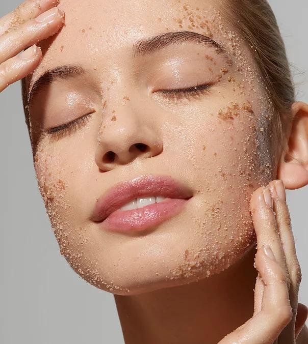 skincare model exfoliating her face with a facial scrub  facing fertility skincare blog
