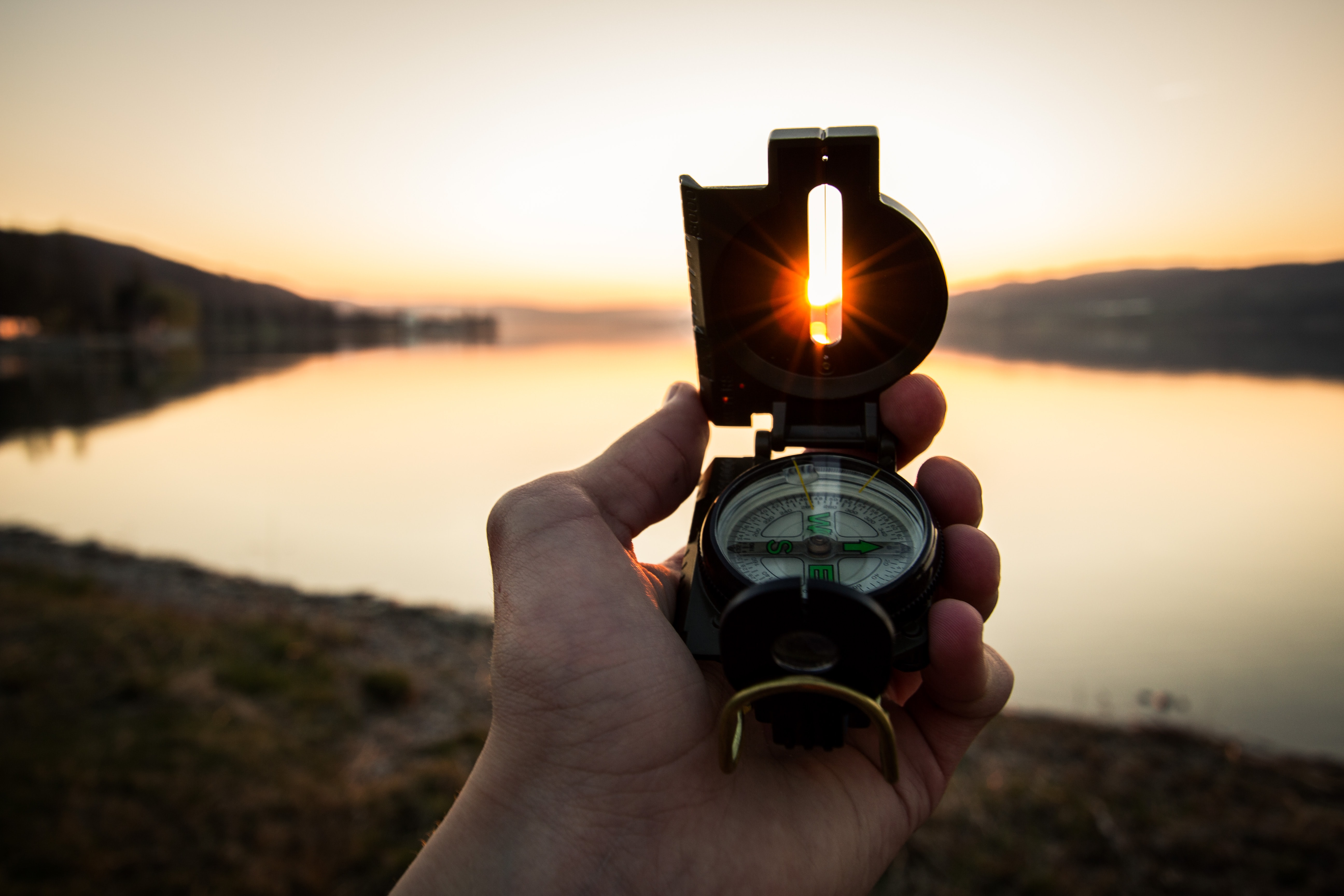 Image - A compass held in hand, facing a sun rise