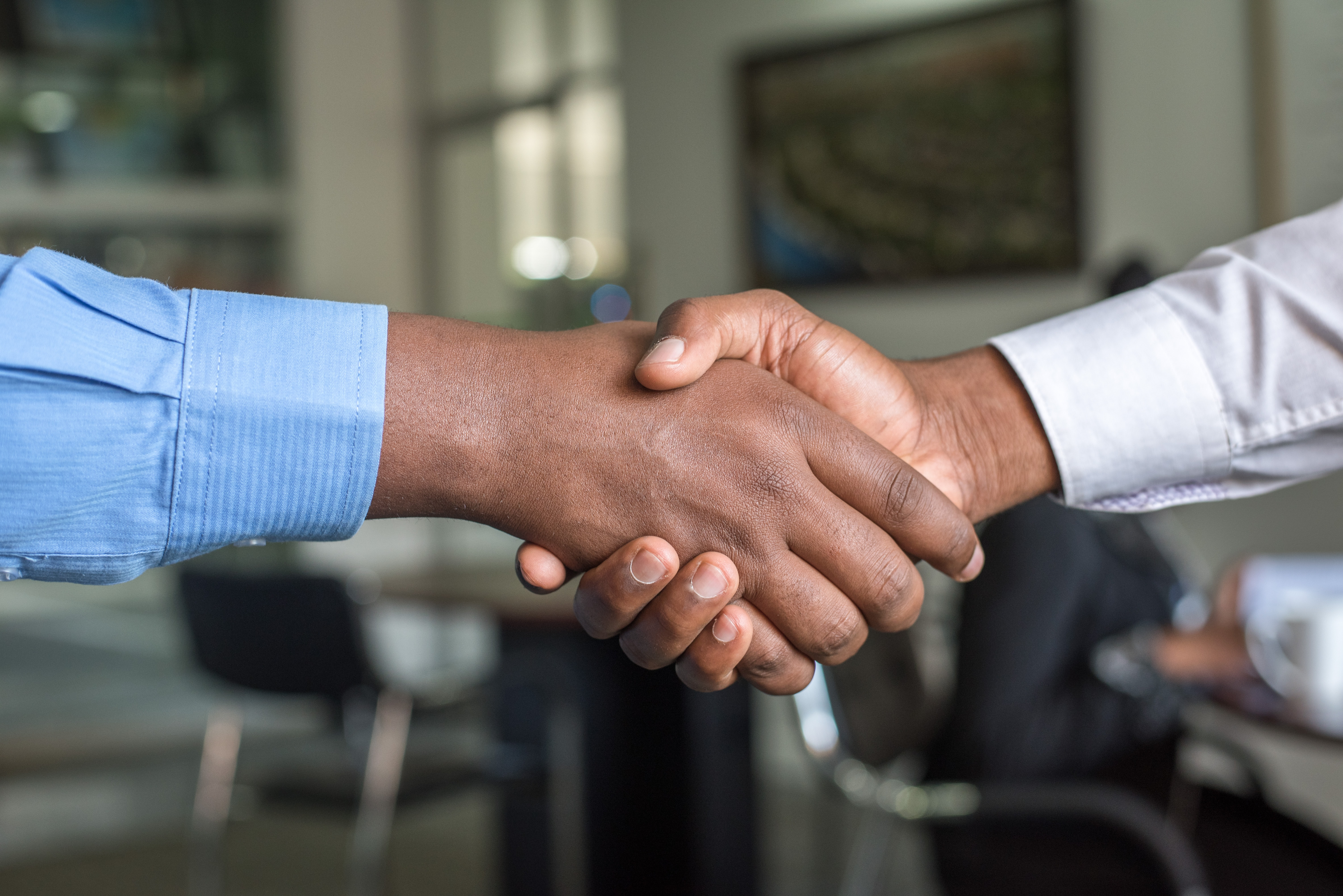 A hand shake between two white collar workers