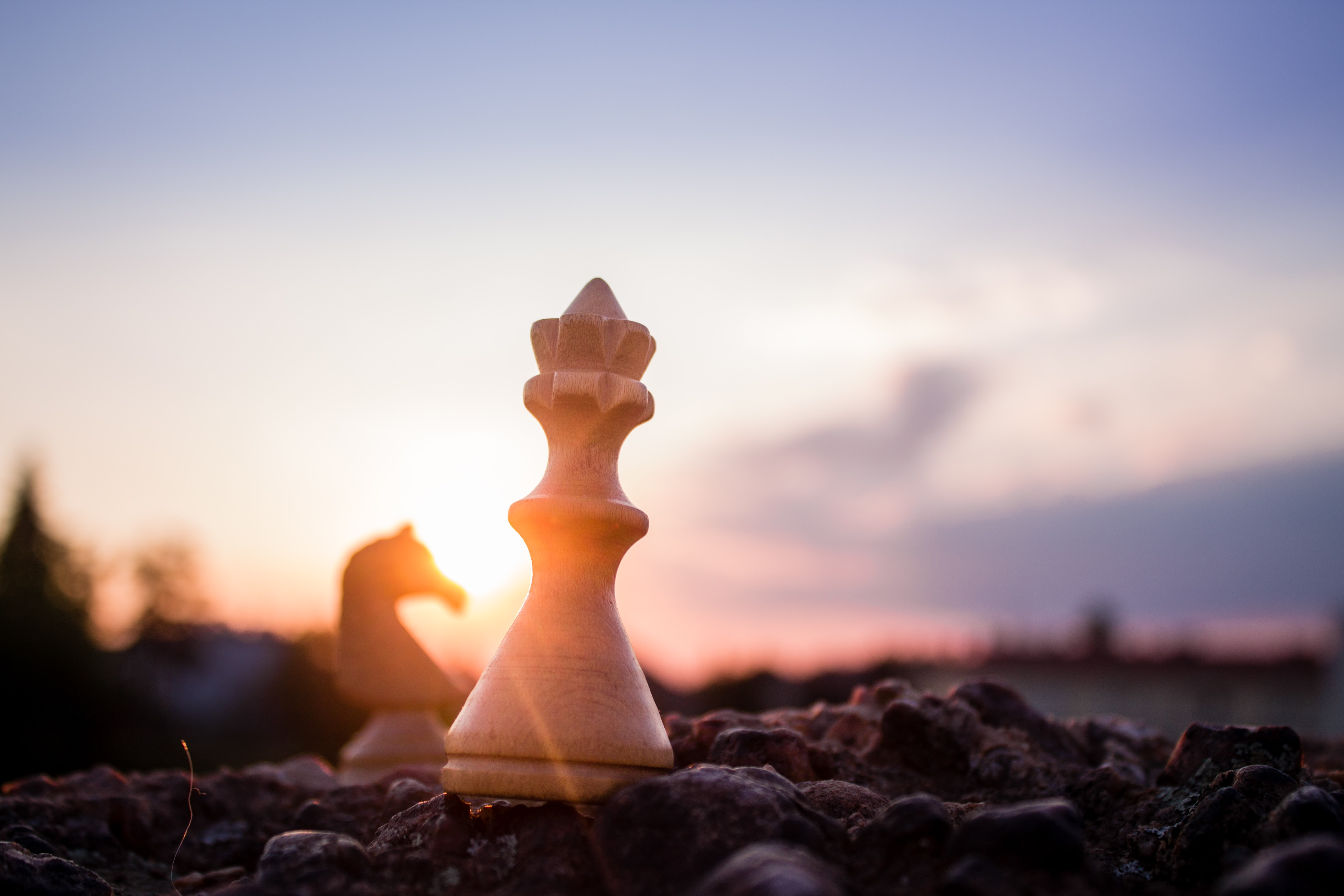 A Large chess piece on a chess board, under a sunset