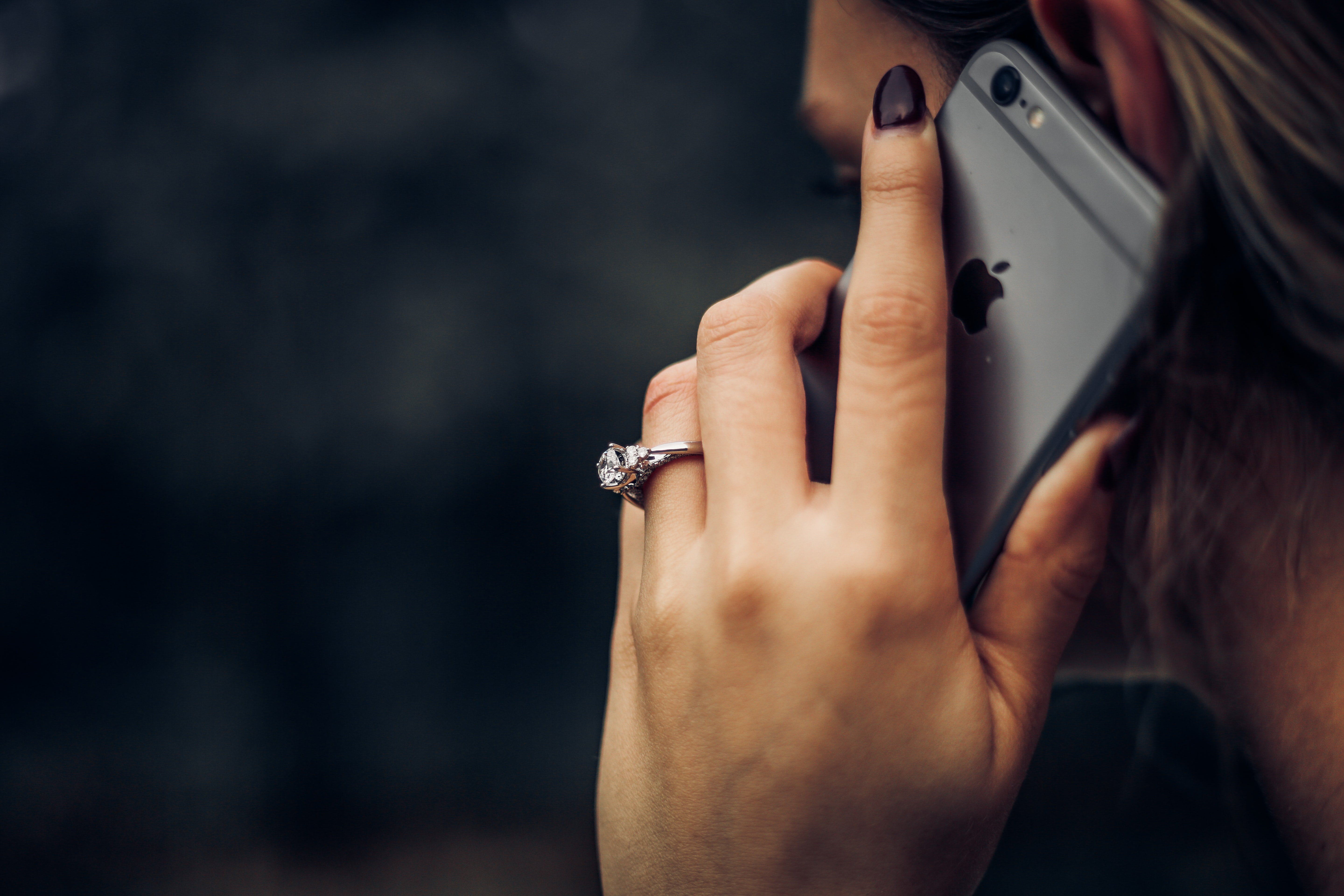 A women holding a phone close to her ear. A large diamond ring is on her wedding finger