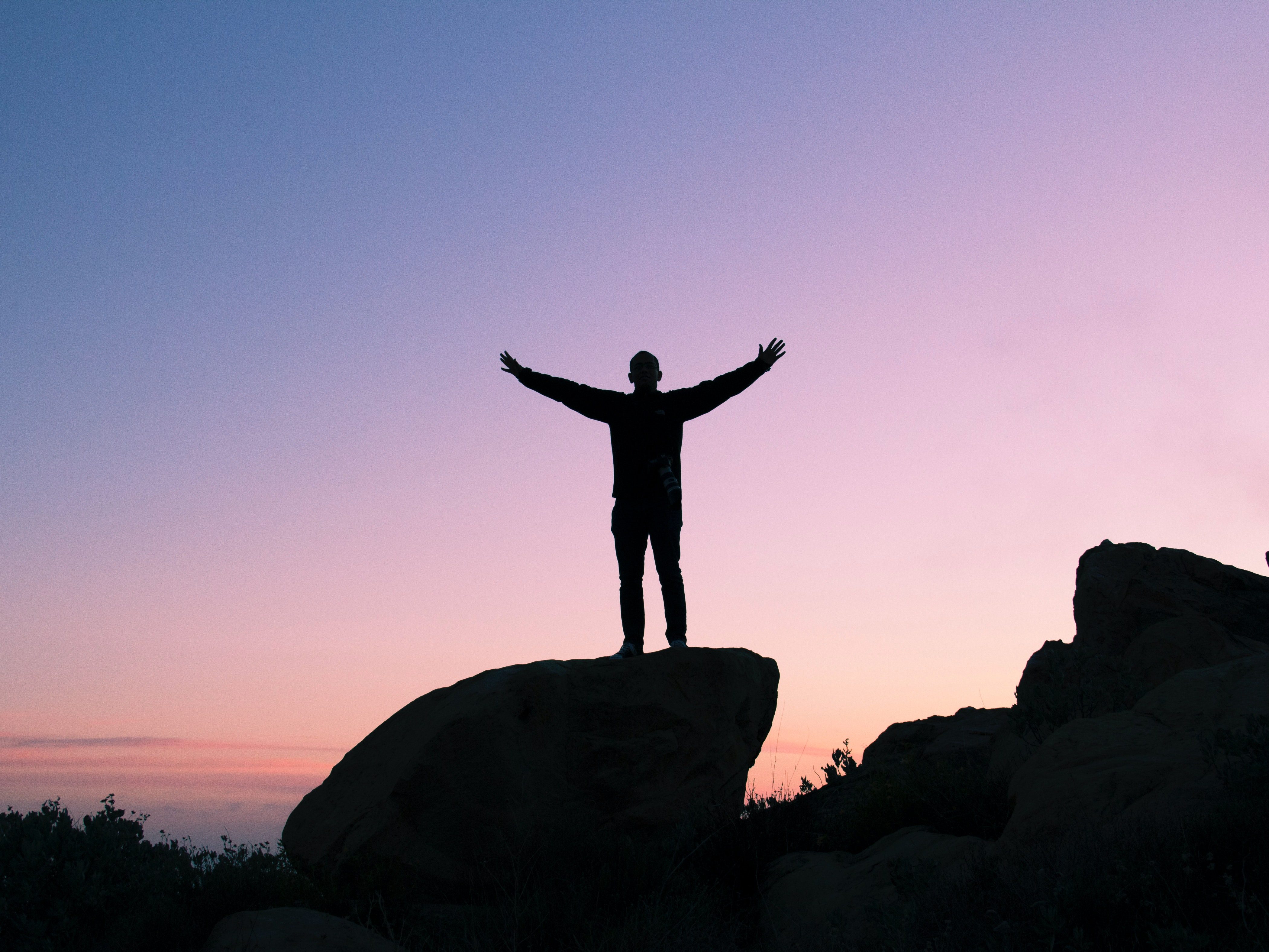A man standing on a large boulder with his arms wide open. The sun is just starting to rise and there is a beautiful purple haze