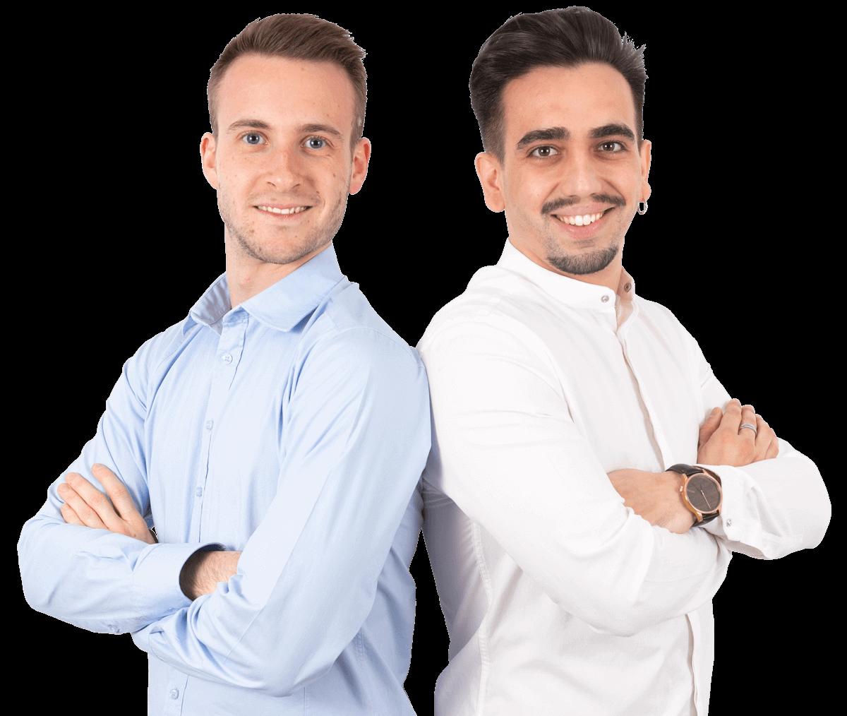 due ragazzi in posa che sorridono. Quello a sinistra è biondo con camicia azzurra, quello a destra è moro con camicia bianca.