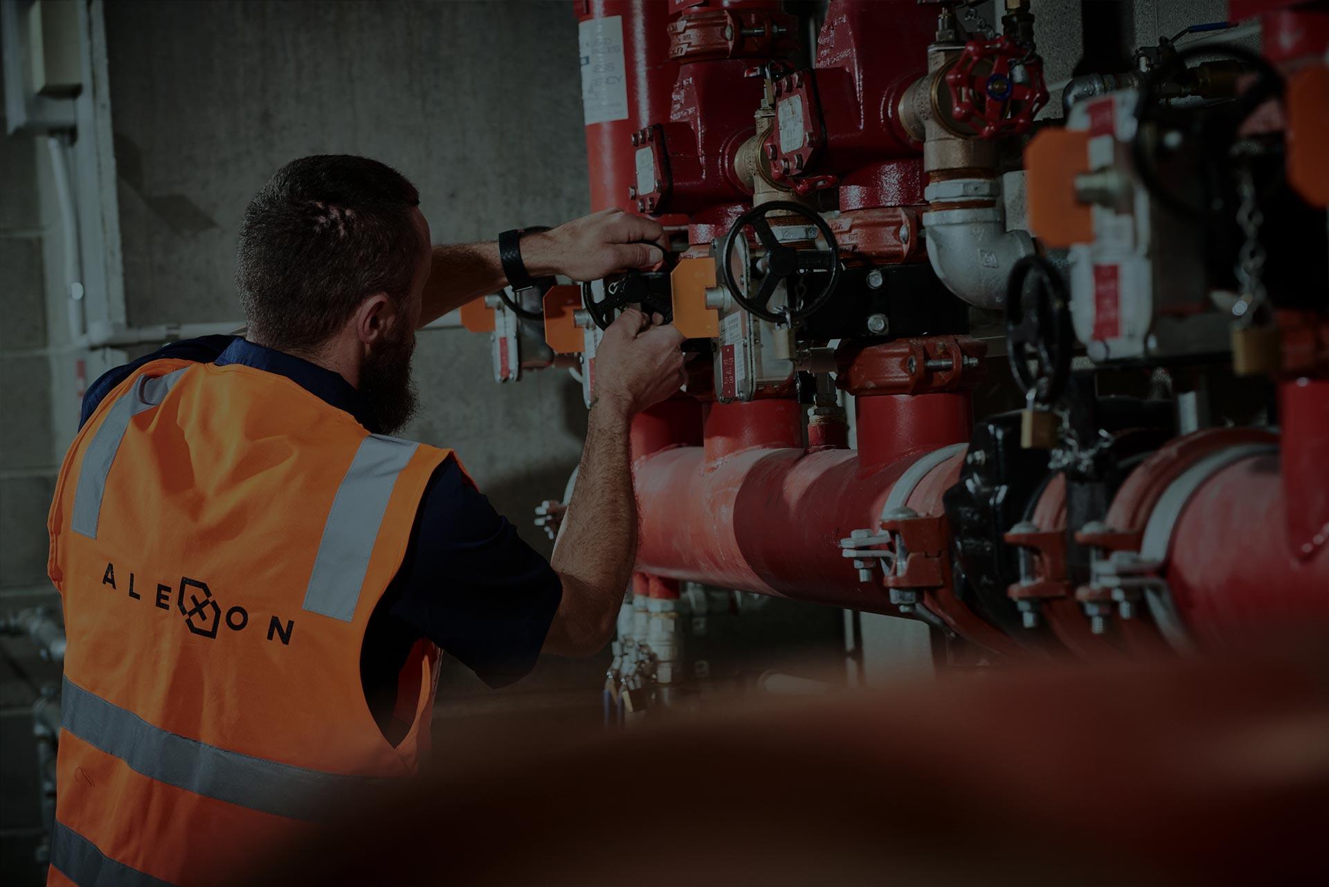 Alexon employee wearing Alexon branded safety gear doing maintenance work.
