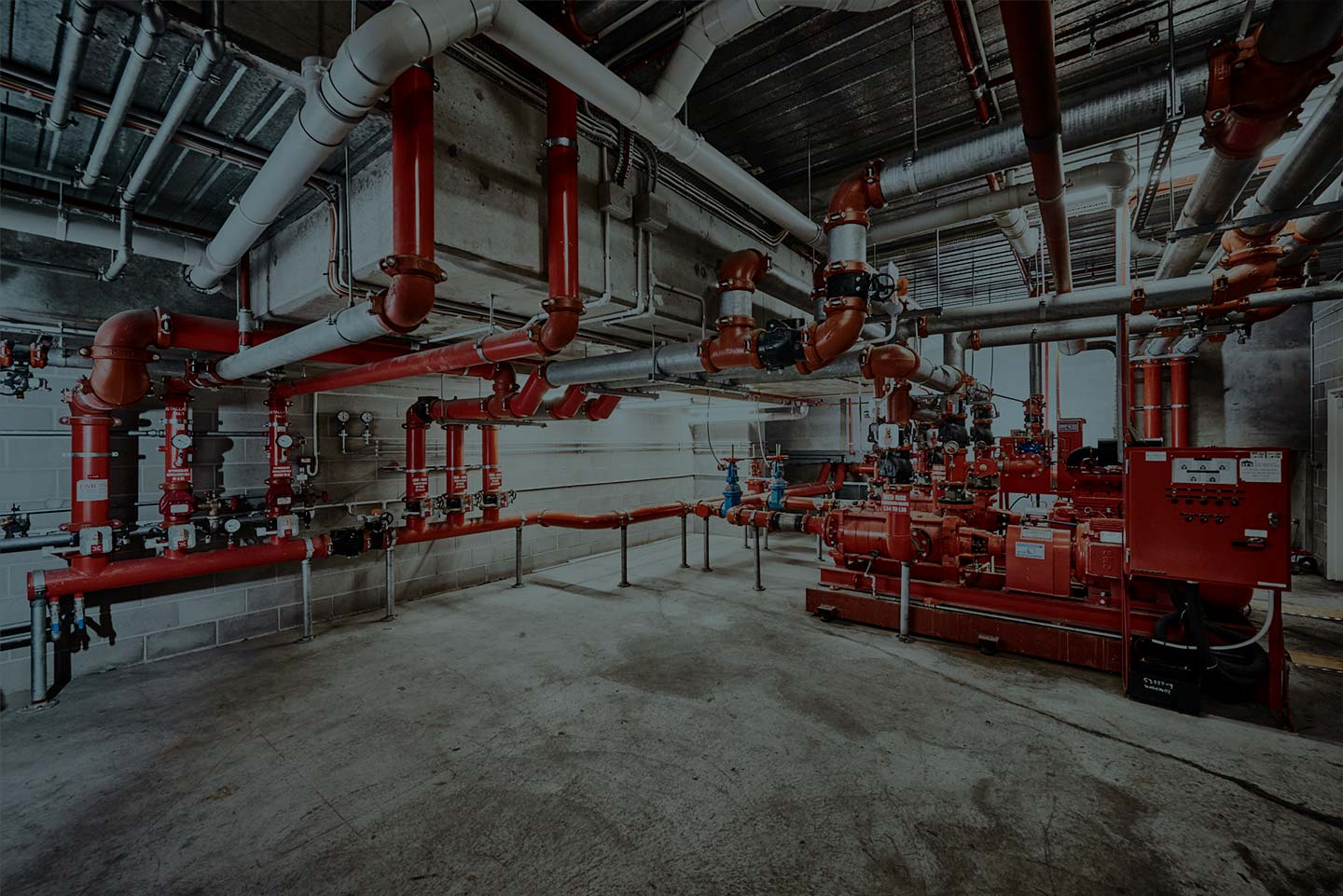 A photo of a sprinkler system control bay under a building.