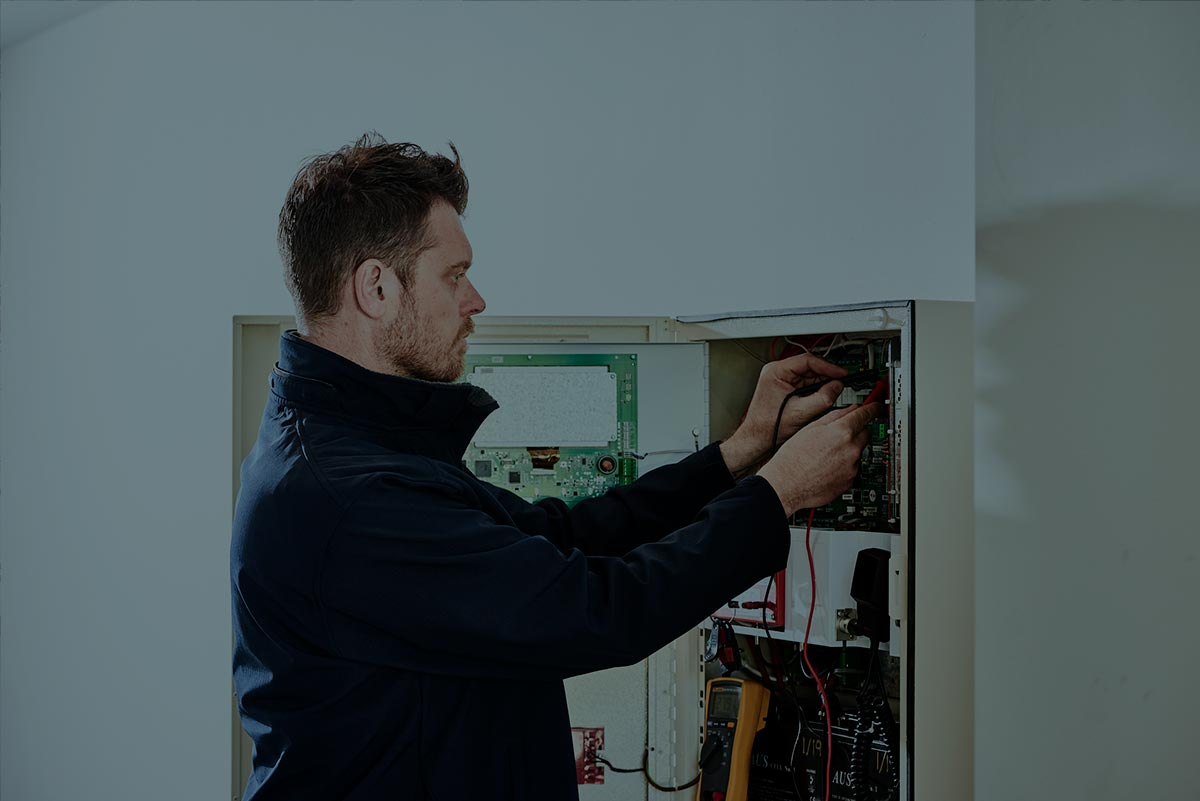 An Alexon employee performing a maintenance check on an electrical fire systems control panel.